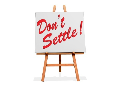 "A sign on an easel reads ""Don't Settle"" referencing the idea of settling for less than what you deserve in a relationship"