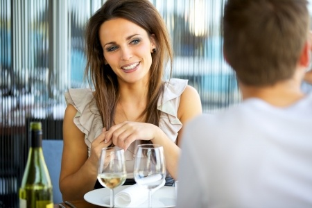 A beautiful woman is sitting across the table at a restaurant on a date with a man.