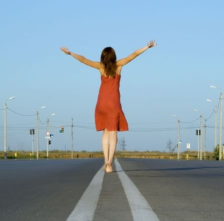 A beautiful brunette woman is walking down the road with her arms extended in joy, happy from the true joy she has found after walking away from a bad relationship.