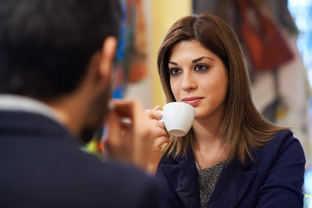 A beautiful woman is sipping coffee while talking with a man over lunch, wondering why she's not getting what she wants in a relationship.