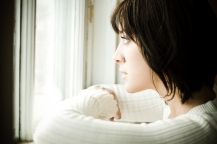 A beautiful woman looks out a window, wondering if she should wait for a commitment or move on from her boyfriend.