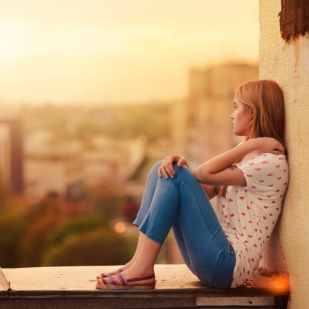 A beautiful woman sits on a balcony overlooking the city devastated that her relationship with her boyfriend has become a long distance relationship