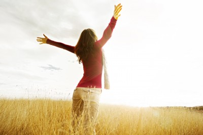 A beautiful woman is rejoicing as she runs through a field in the sunlight.