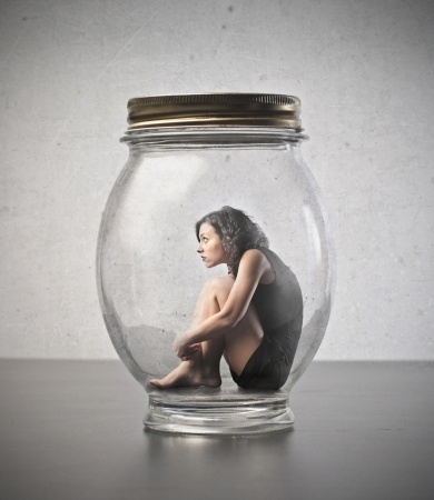 A beautiful woman sits inside of a giant glass jar symbolizing that she feels trapped by her need for external validation.