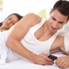 Man is cheating on his girlfriend texting the other woman while she sleeps in bed next to him.