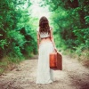 A beautiful woman walks down a path with her suitcase symbolizing that she is breaking free from an emotionally unavailable man who won't commit