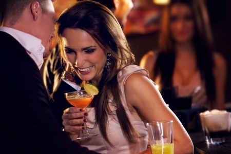 A beautiful woman is feeling a strong connection with a man at a cocktail party.