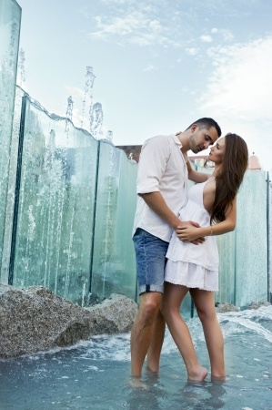 A beautiful woman and a man are sharing a romantic kiss in front of a fountain - love concept.