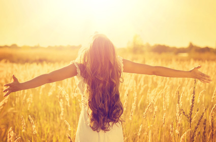 A beautiful woman is in a field with her arms outstretched facing the sunshine realizing that there's nothing wrong with her.