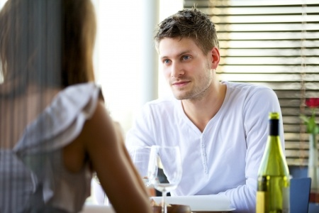 A man and a woman are having a serious discussion over dinner while he is telling her his side of the story.