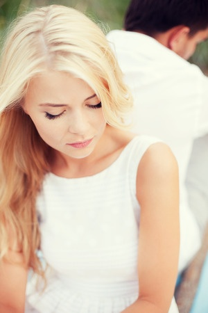 A beautiful blond woman is sitting with her back to her boyfriend as they break up.