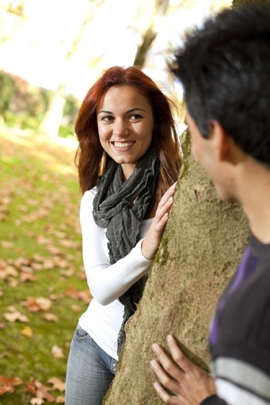 A beautiful woman is standing next to a tree in a park smiling at her male friend, wondering how to get out of the friend zone.