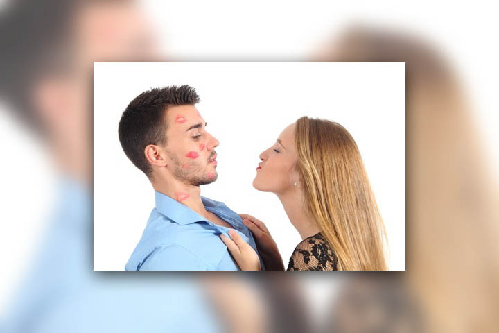 A woman is chasing a man covering his face with kisses.