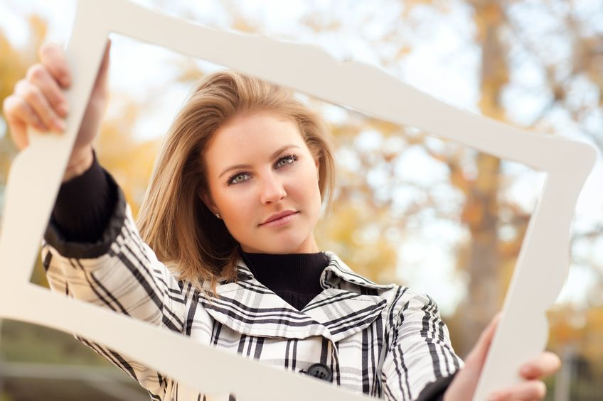A beautiful woman is holding a picture frame in front of herself.