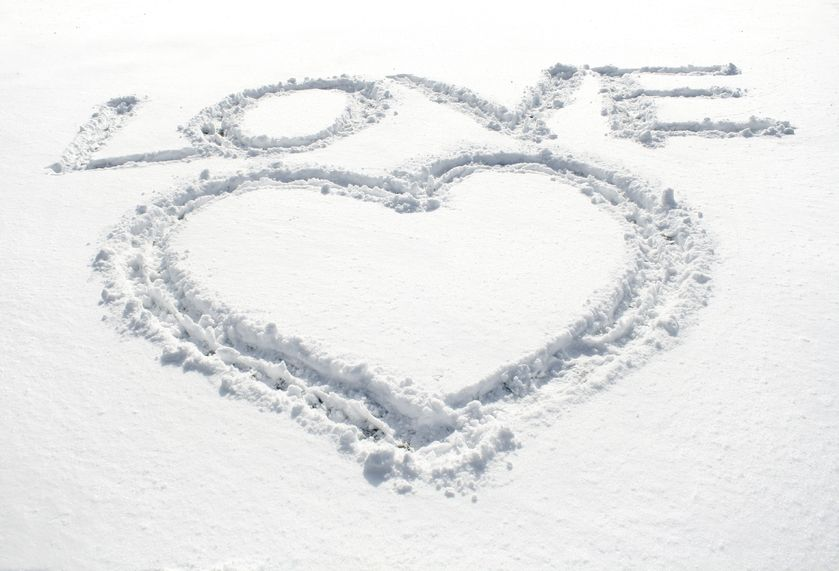 The word love and a heart symbol written in snow.