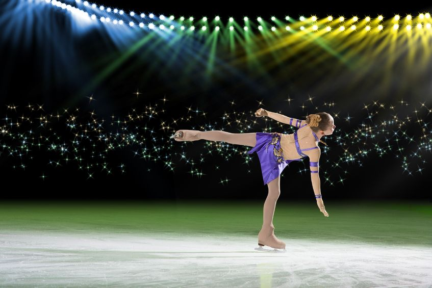 A beautiful young woman is figure skating, building her confidence and enjoying her passion.