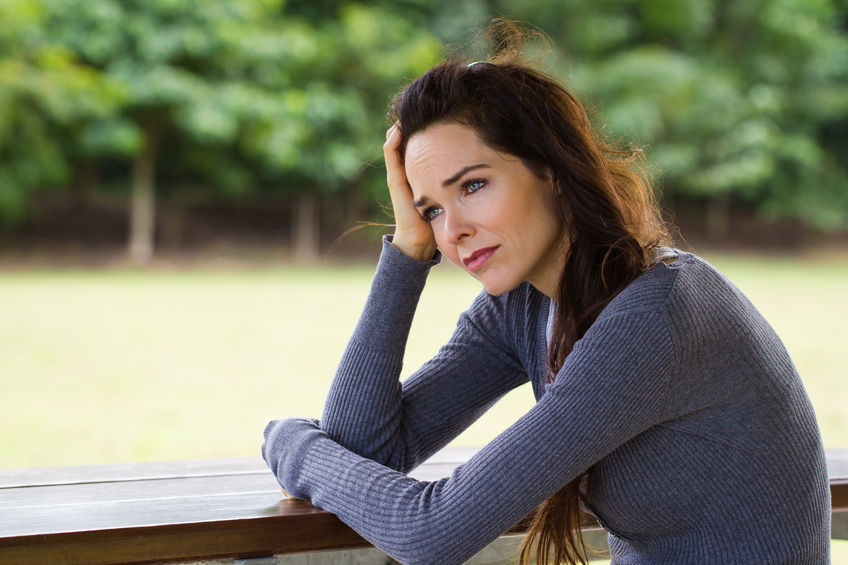 A beautiful woman sits on a deck feeling frustrated at her boyfriend for acting like a man child.