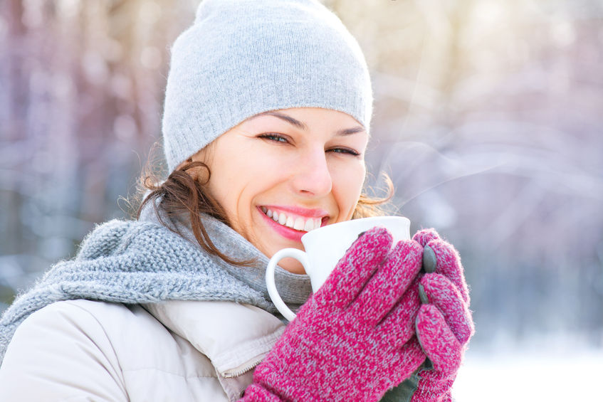 A beautiful woman is happy drinking  a cup of coffee on a winter day near Valentine's day.