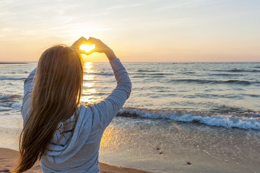 A beautiful woman holds her hands out in the shape of a heart while watching the sunset at the beach.