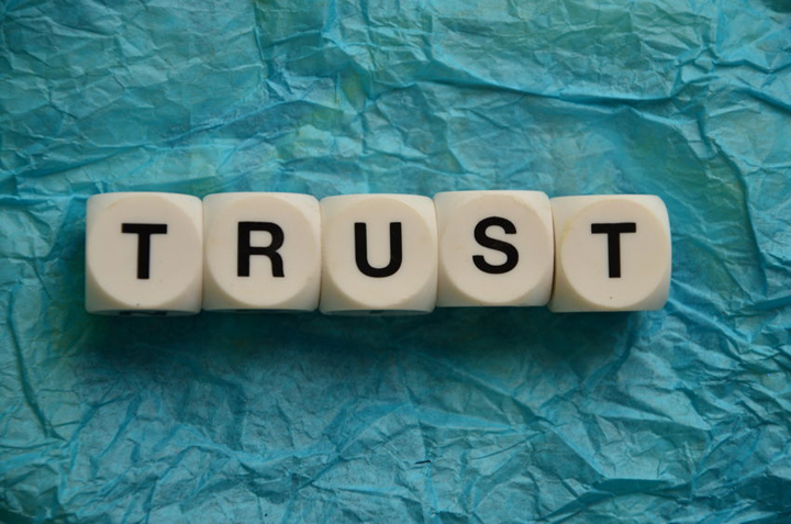 The word trust in letter blocks on tissue paper.