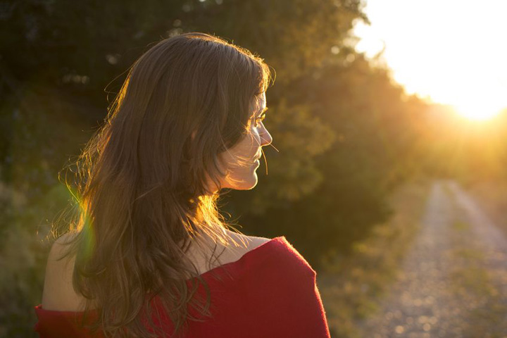 A beautiful woman walks down a path towards the light symbolizing trying to move on from a man who won't commit.