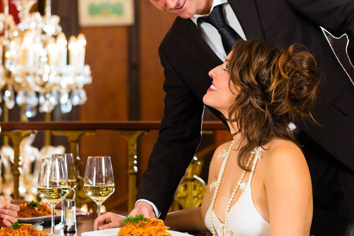A beautiful, confident woman sits smiling at the table in a fine restaurant while the waiter delivers her food.