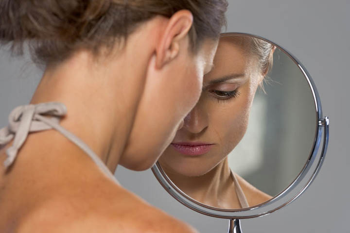 A beautiful woman looks in a mirror wanting it to be the way it was.