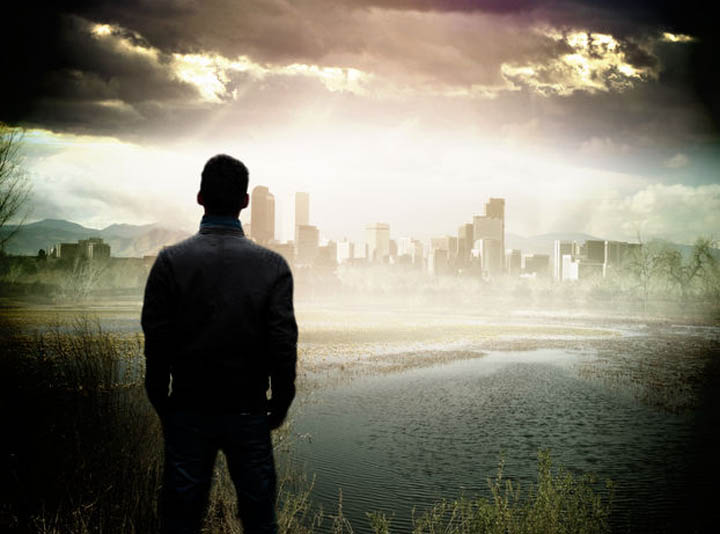 A man stands on the edge of a pond looking at the city in the distance.