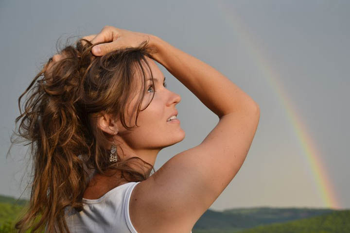 A beautiful woman looks at the sky with a rainbow in the distance symbolizing hope.