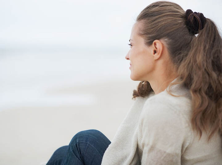 A beautiful woman looks out over the beach, wondering why her boyfriend suddenly disappeared.