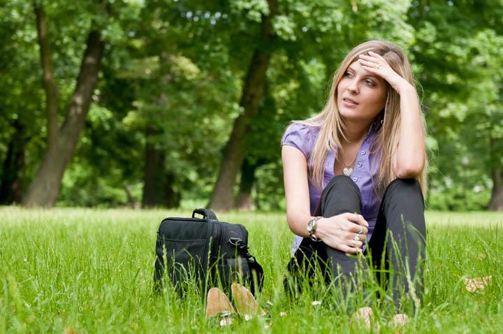 A beautiful woman sitting in a field feeling desperate about her boyfriend.