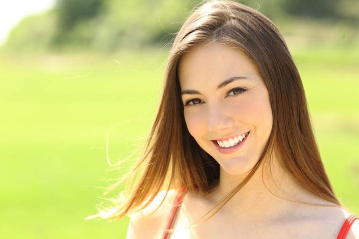 A beautiful woman smiling in a park.