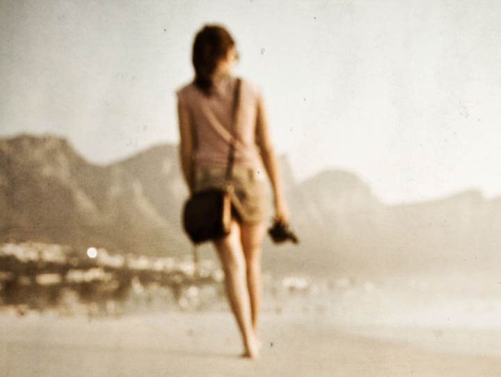 A beautiful woman is walking on the beach trying to become unlost.