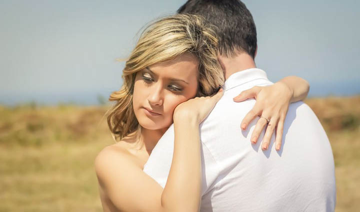 A beautiful woman is hugging her boyfriend, wondering why he's getting emotionally distant.