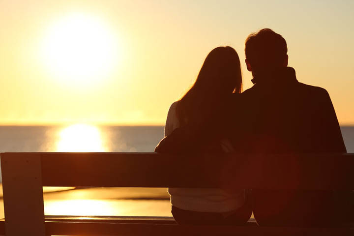 Silhouette of a woman and man watching the sunset over the ocean.