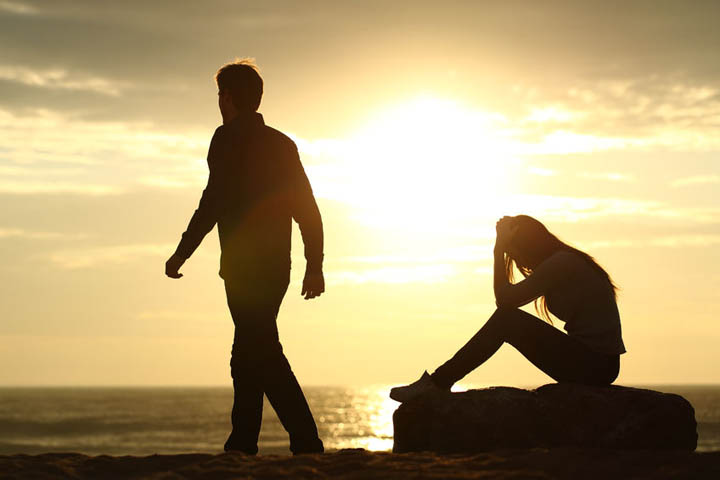 Silhouette of a woman with her head in her hands while her boyfriend walks away.