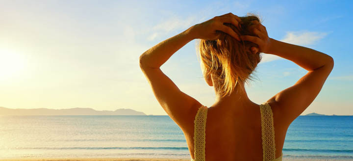 A beautiful woman holds her hair up while looking at the ocean.