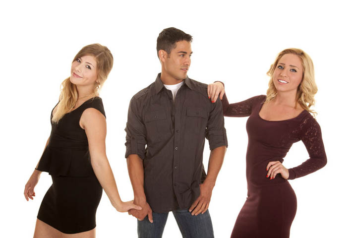 A guy is holding hands with one woman, while checking out and flirting with another woman
