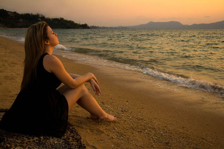 A beautiful woman is sitting on a beach looking at the ocean, wondering when he'll commit.