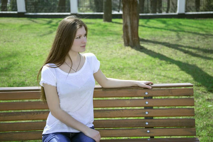 A beautiful woman sits on a bench in a park by herself.