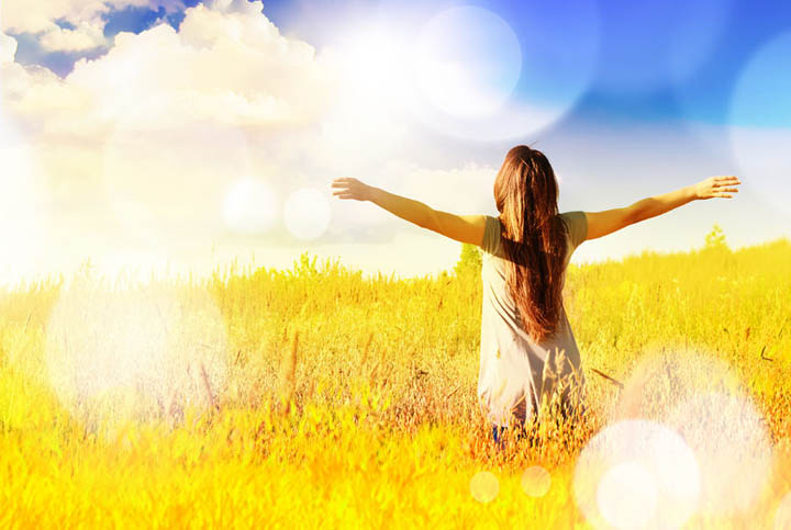 A beautiful, exuberant woman is in a field with her arms raised towards the sun.