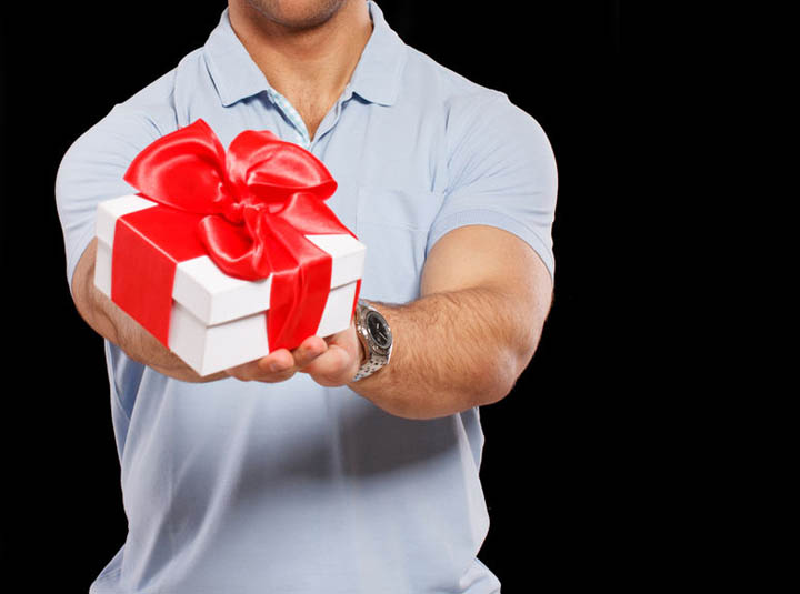 A nice guy is holding a gift for his girlfriend.