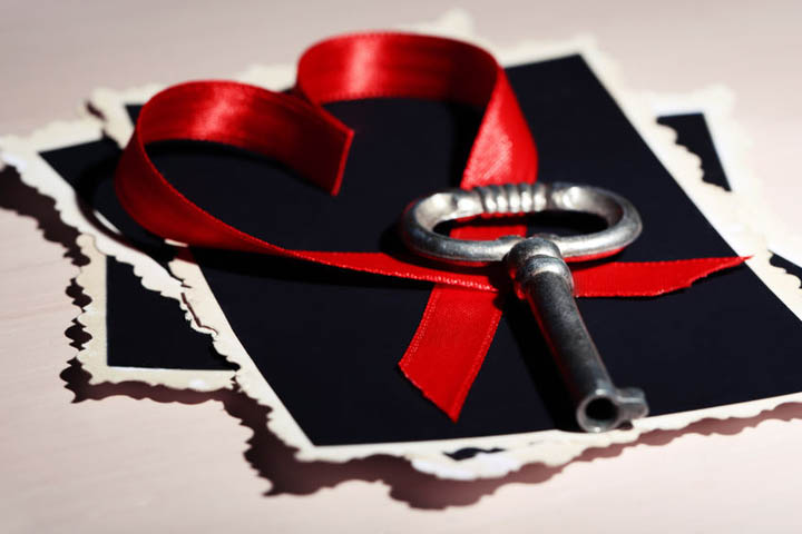 A key lies on a table next to a red heart made from a ribbon.
