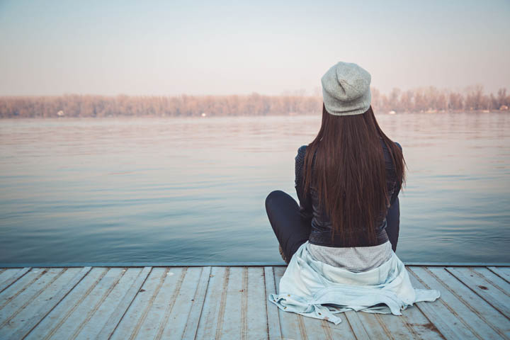 A woman sits on a pier looking at the lake - autumn scene.
