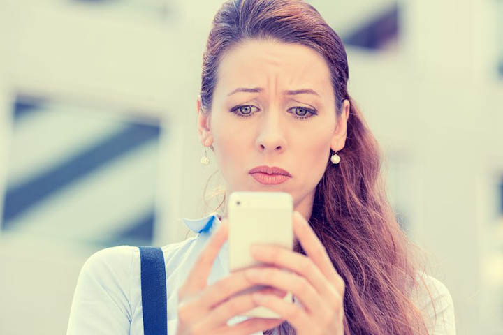 A beautiful woman looks at her phone, worried, wondering if she should call or text him.