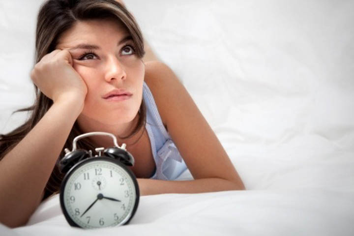 A beautiful woman is looking frustrated near a clock, wondering how much longer she needs to wait for her boyfriend.
