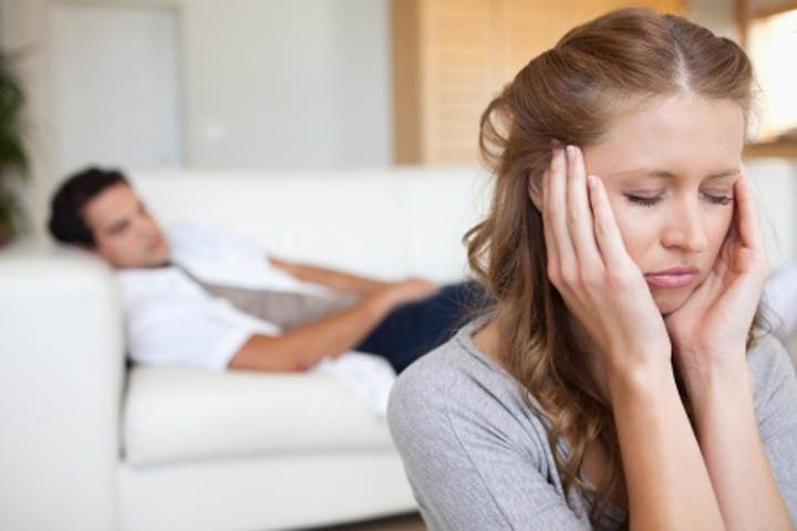 Man lies on the couch while his girlfriend is upset with him because he's emotionally unavailable.