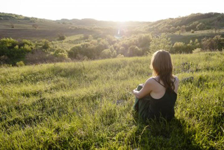 Woman sitting and relaxing in a field, looking at the sun.