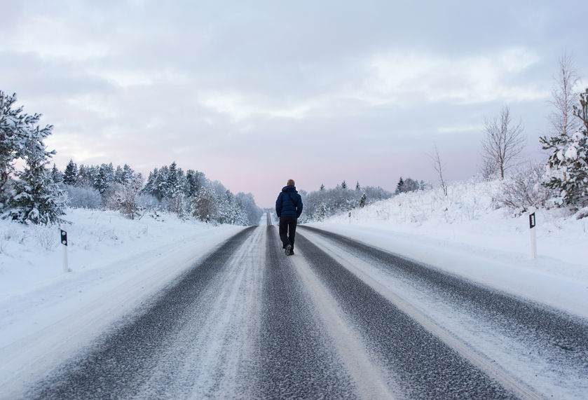 A man walks down a snowy winter road.