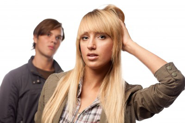 A blond woman scratches her head because she's confused by her boyfriends actions.